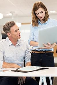 Collègues de travail regardant un pc portable Gestion de patrimoine