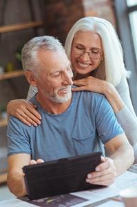 Couple de retraité regardant une tablette tactile Gestion de patrimoine